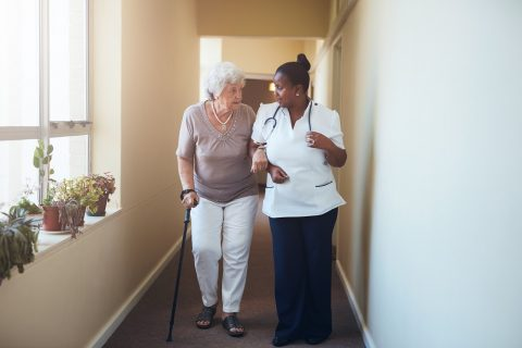 Older adult walking with medical professional